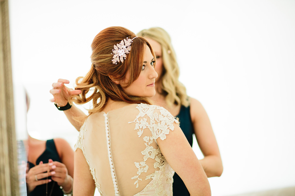 the bride looks over her shoulder into the mirror