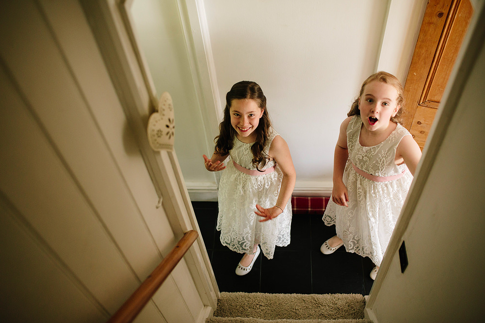 the flowergirls look up to see the bride coming down the stairs
