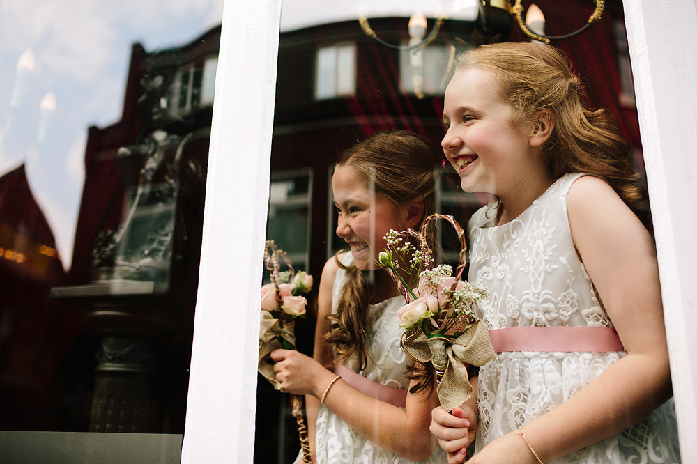 the flowergirls look through the window at the bride arriving