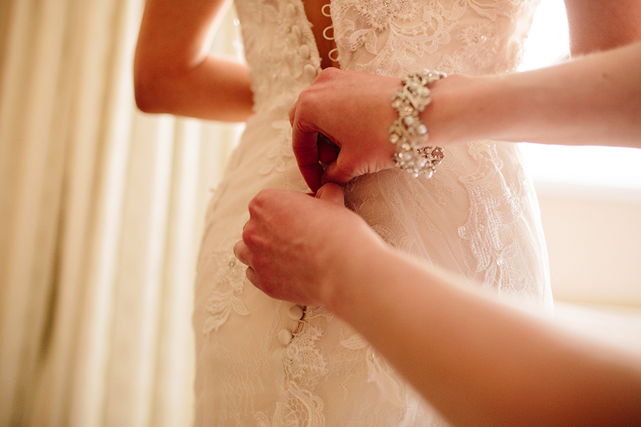 the bride has her dress buttoned up