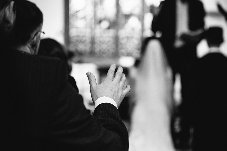 a hand is held up to bless the couple