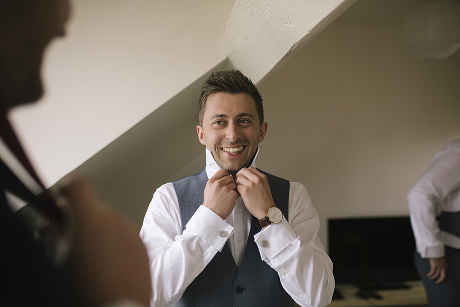 the groom smiles as he ties his tie