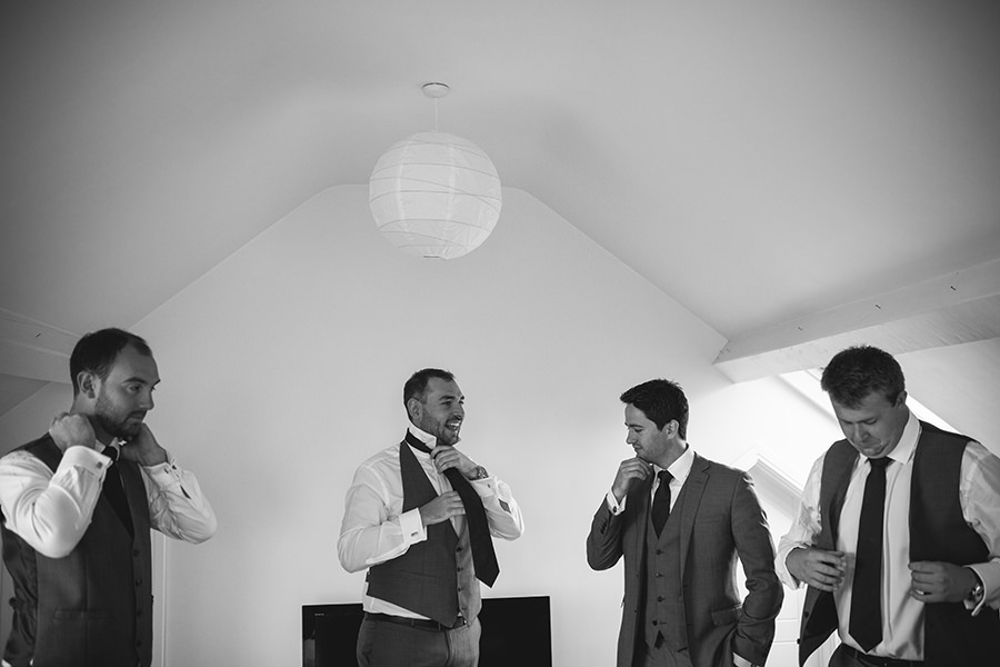 the groomsmen help each other get dressed