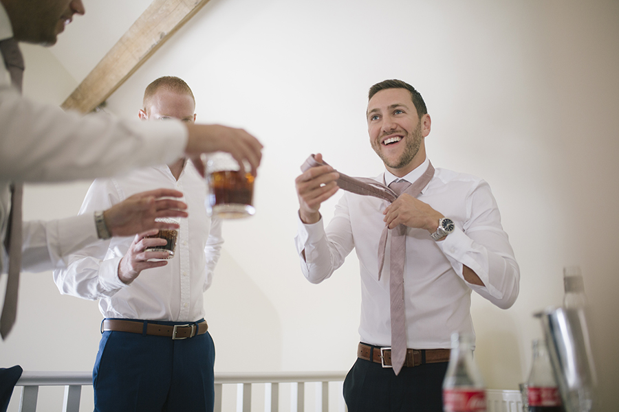 the groomsman laughs to his friend